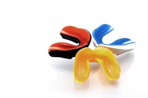 Drei Zahnschutz Schienen für den Sport in den Farben Gelb, Blau-Weiß und Rot-Schwarz